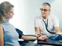 врач меряет девушке давление