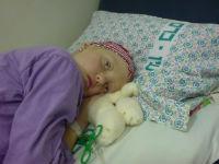 Больной ребенок после химиотерапии лежит на кровати
