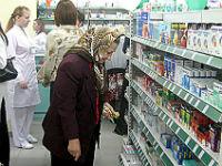Женщина выбирает лекарство в аптеке