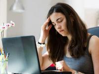 Уставшая женщина работает за ноутбуком