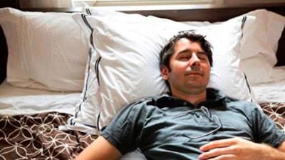 мужчина спит на нескольких подушках