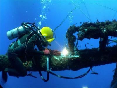Водолаз сваривает трубу под водой