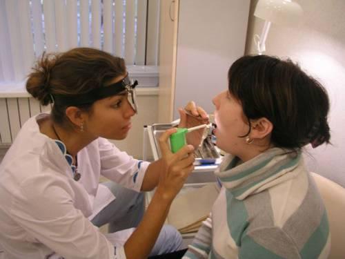 Врач осматривает горло пациента