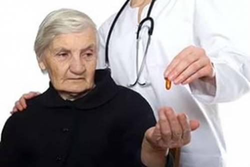 Врач дает лекарство пожилому человеку