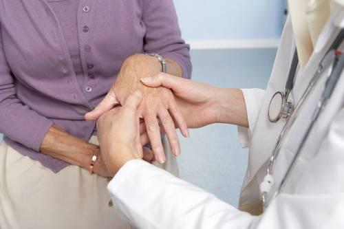 Врач осматривает пальцы рук пациента