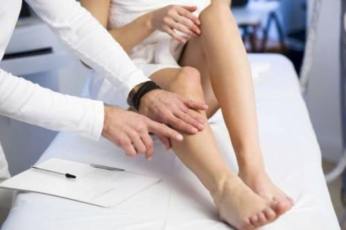 Врач осматривает ноги пациента